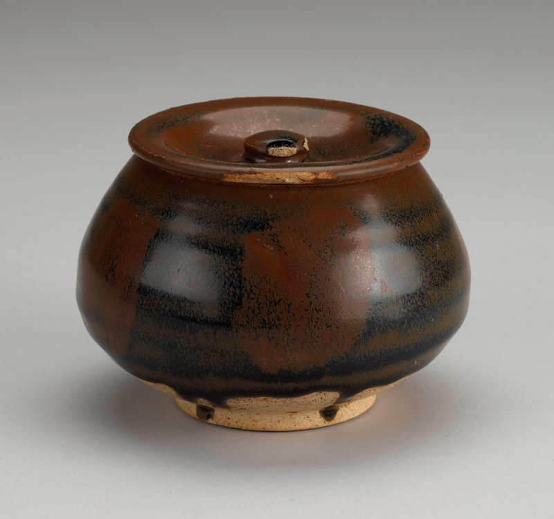 black and rust streaked and spotted glaze; footed jar, with low outward flare, flaring in to mouth; concave cover with small knob