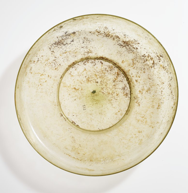 clear glass with yellowish tint; several areas of iridescence; tall sides