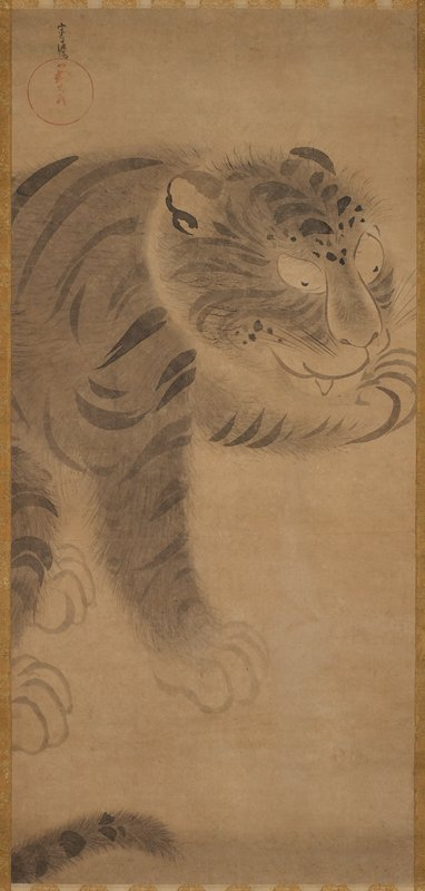 seated tiger licking front PL paw; brown and gold brocade border