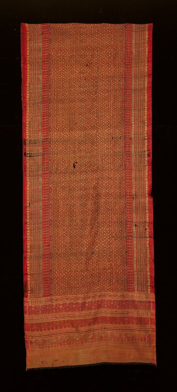 ikat; purple, red, green, yellow; central rectangular field of polychrome interlocking diamond patterns flanked on either long side by smaller similar design stripes; six bands at either short end, every other band has same design as central field only bound by banding edges