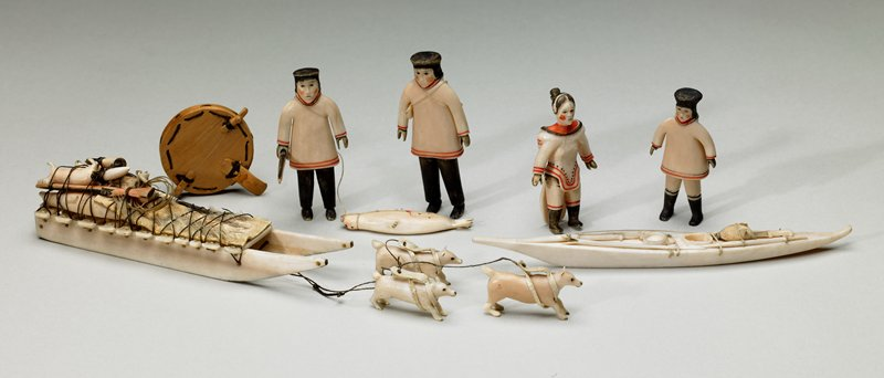 dog sled outfitted with scraper, rifle, powder horn, spear, cord and animal hide cover; four animal carcasses attached to sled; two dogs with leather harnesses attached to sled with thread; third dog with harness has become detached