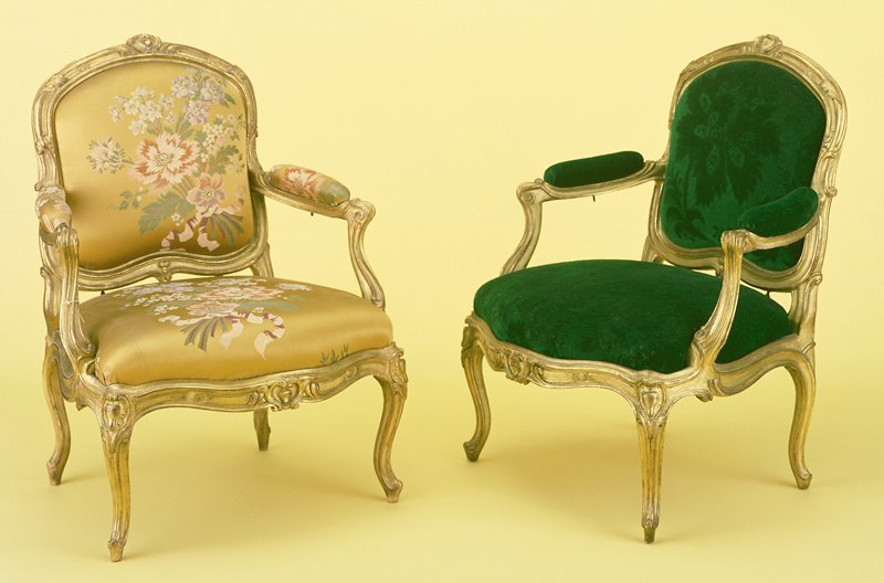 Set of Eight Louis XV Fauteuils, giltwood with detachable cartouche-shaped backs, upholstered arm-rests and serpentine drop-in seats. Backs with broad molded frames edged with scrolls interrupted by foliate sprays and centered by cabochon and cartouche crestings with outscrolled arm-supports, waved seat-rails of undulating outline centered by trefoil cabochon cartouche clasps on molded cabriole legs headed by similar clasps. Four stamped I. Lebas. Six are covered in polychrome gilt ground floral brocade and two are covered in dark green floral patterned velvet.