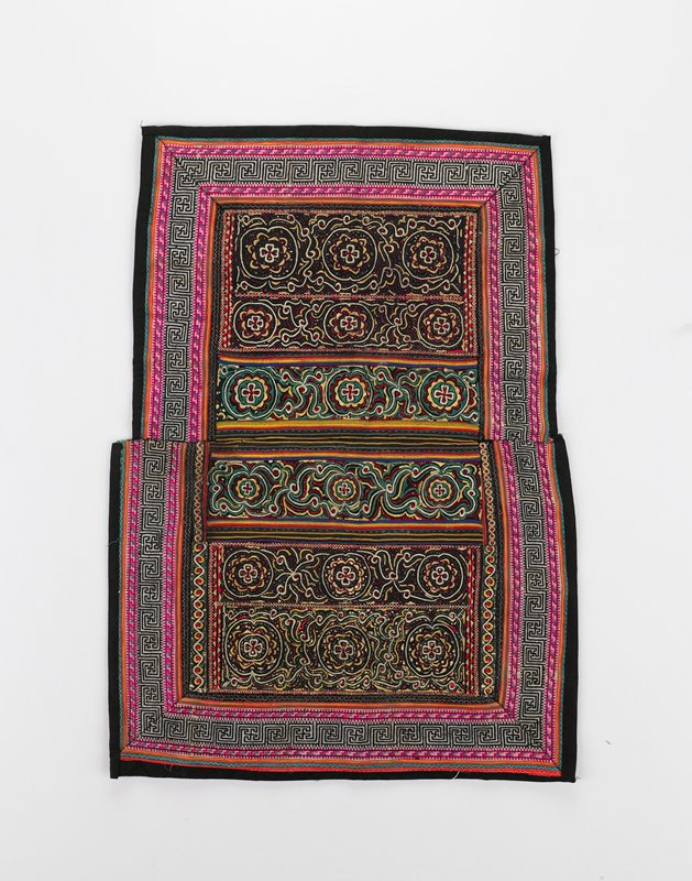 black backing; applique bands at center in organic designs; cross-stitch geometric pattern borders