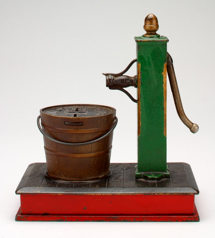 green water pump with big brown bucket on brown and red rectangular stand