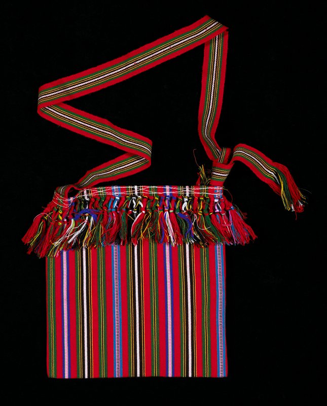 Red vertical stripes and blue, black, white and green stripes divided by thin yellow stripes. decorative fringe around the edge organized in sections with two knots; striped ribbon strap.
