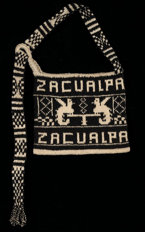 Wool knitted bag; off-white with black design of quetzal bird and letters on both sides; wool strap.