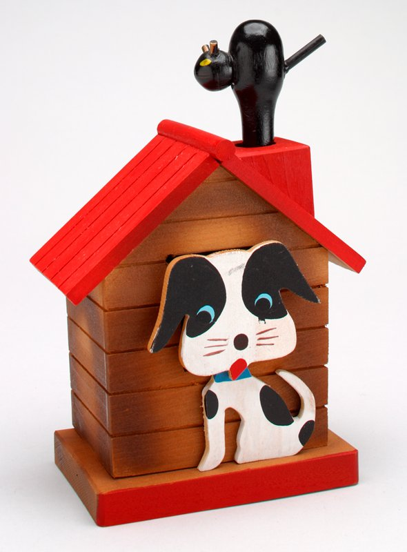 wooden brown dog house with red roof; arching cat standing on chimney, white and black spotted dog stands in front of house; coin slot covered by dog's head; depressing the cat makes the dog's head move downward exposing slot--release and cat and dog return to original position with a squeaking noise