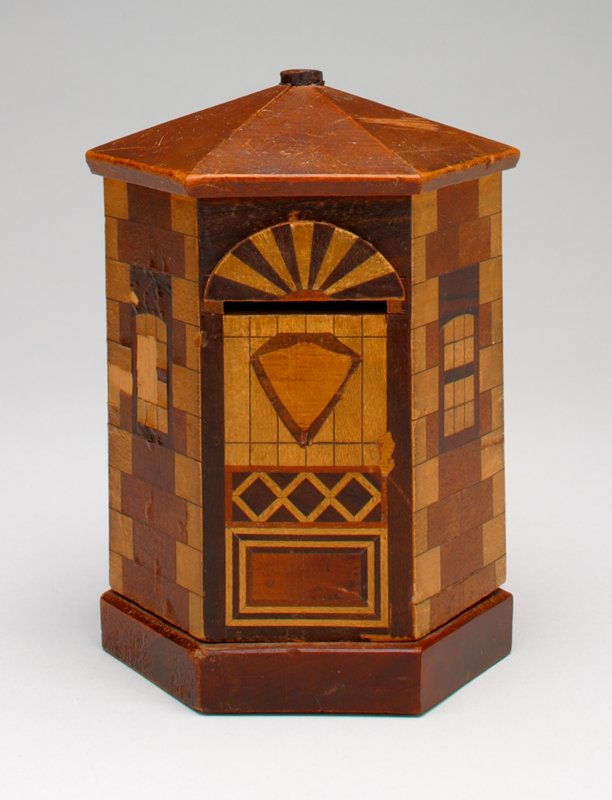6-sided building bank with marquetry veneer, forming bricks, windows and designs in different colored woods on all sides; building is on a 6-sided platform