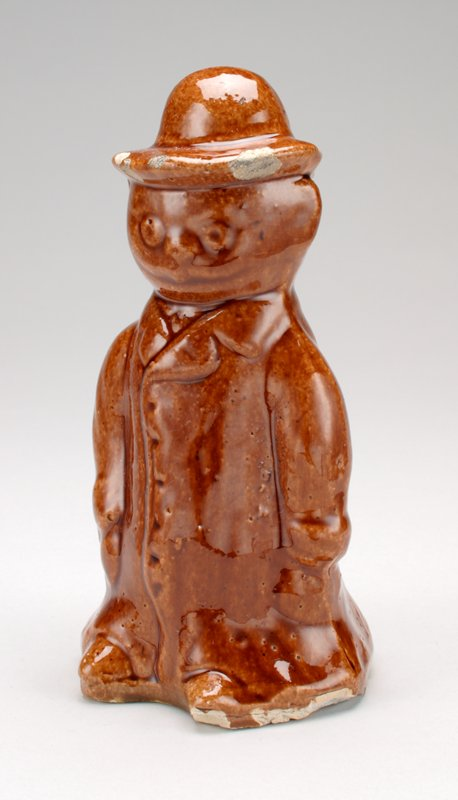 brown standing man bank with shiny glaze; man is wearing a long buttoned-up coat with feet showing under; man is wearing homburg hat; round eyes and nose; smiling