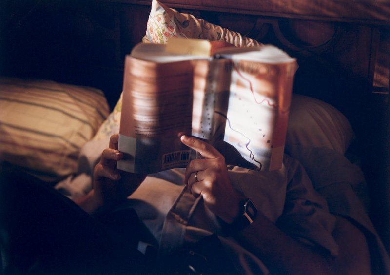 person reading in bed and holding book up in front of face; Kodak film text across top; image area edge irregular
