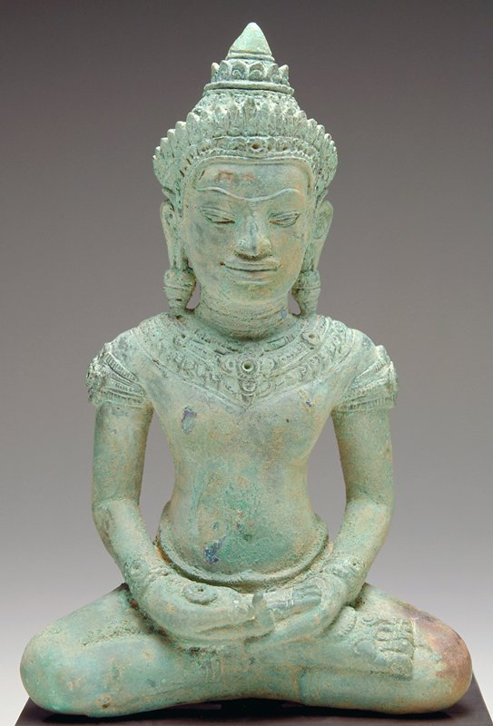 seated Buddha with hands in lap, PR index finger bent to touch thumb; wearing crown, necklace, bracelets and heavy earrings