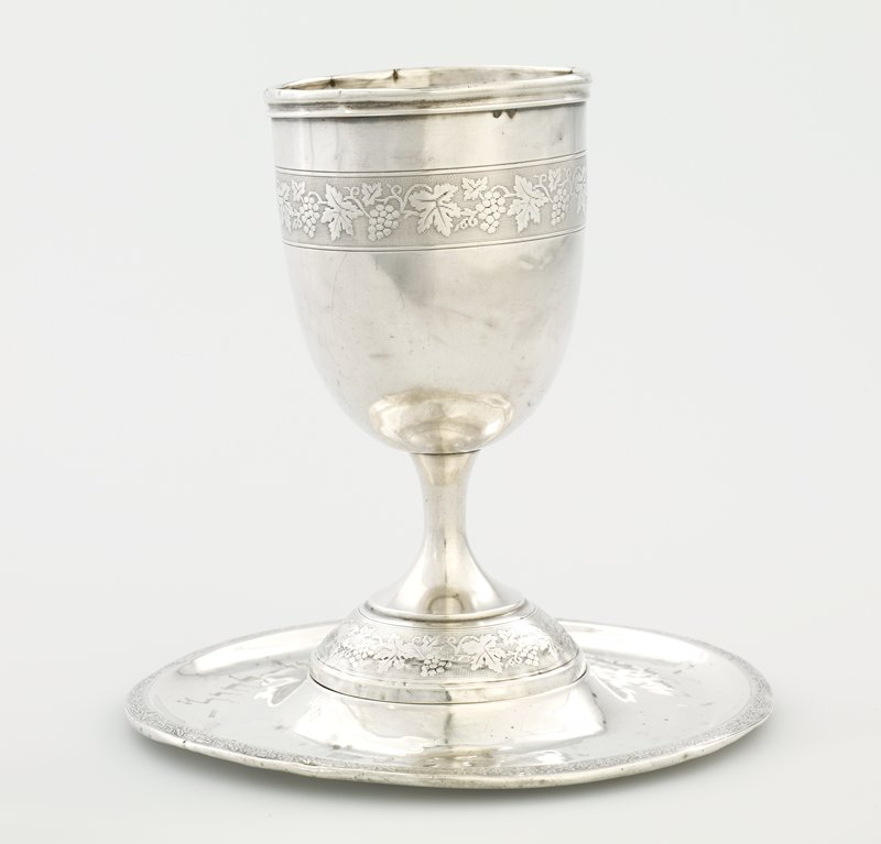 goblet-style cup with foot and stem; decorated at foot and body with bands of grapes, leaves and vines; saucer with raised center; rim decorated with grape motif from cup; Hebrew insription on one side