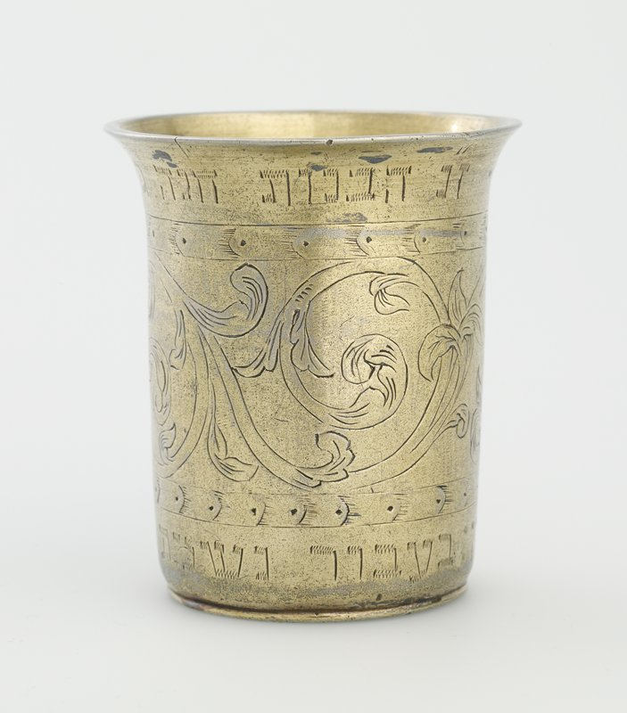 small tumbler-style cup with outward turned lip; decorated on exterior with incised floral band flanked by Hebrew text