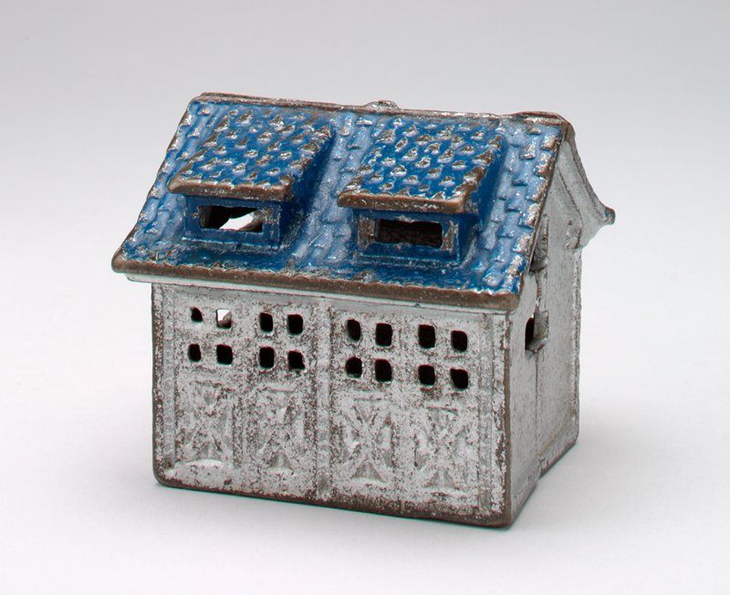 cast iron bank in a building shape with a blue roof with two dormers on each side; there are two double doors on one side