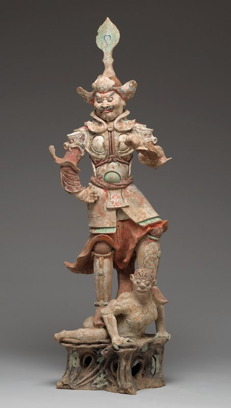 standing male figure wearing armor and tall hat, with thin moustache and beard; figure stands with both feet on a white-skinned demon with fangs, green claws and black hair