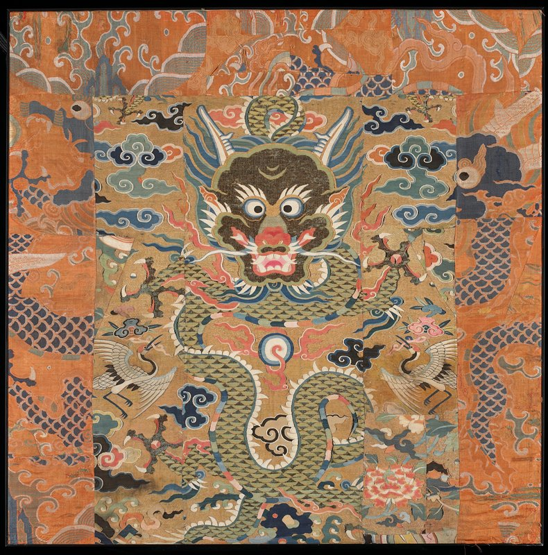 fragments of at least two textiles sewn together; large-headed dragon at center surrounded by clouds and birds; orange and blue fabric with dragon motif around top, R and L edges; received framed