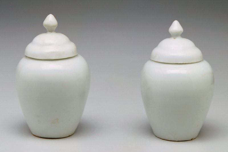 small foot flaring out to a wide shoulder and small mouth opening; lid with small cone-shaped finial; white glaze