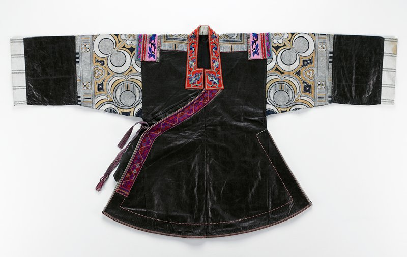 heavily indigo dyed body; curved hem; sleeves and top of shoulders decorated with printed bands with blue, yellow and white circle motifs; embroidered flowers and birds in red around collar and on 2 decorative tails on back; cross-stitch panel at opening on front; floral embroidered strips at shoulder