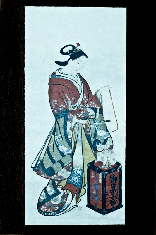 Female figure wearing colorful robes with a design of bamboo blinds and cherry blossoms, holding a cat toy in her left hand and playing with a white adult cat and tiger-like kitten. The cats sit on a box that bears the name of a sweets store in Asakusa.