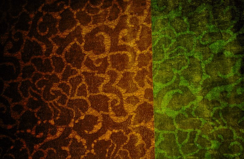 """Cotton velvet batik with scroll and floral design, forground in brown. Vertical pattern repeat at 16"""", horizontal repeat at 23 1/2. Cotton velvet batik, brown/orange background with scroll and floral design, forground in brown. Vertical pattern repeat at 16"""", horizontal repeat at 23 1/2. (Brown)"""