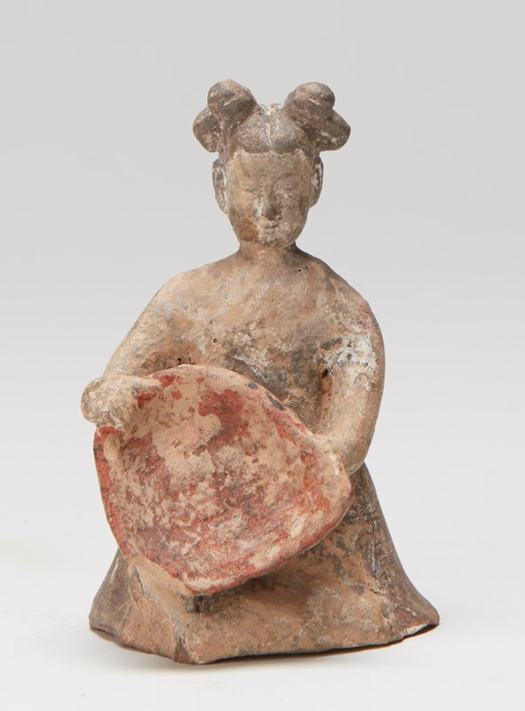 Kneeling figure of woman with winnowings in basket.