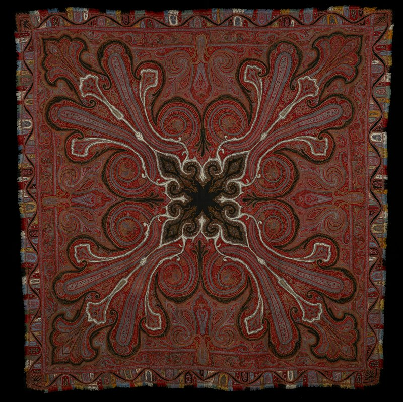 Square shawl, patchwork, of hand-loom woven pieces with inserted scrolls of black and white and river design in border. Field carries pattern of large cones and arabesques converging on the shaped central panel. Inner border has running flower and leaf design. Outer border embroidered. Fringed edges. #9 in Exhibition.