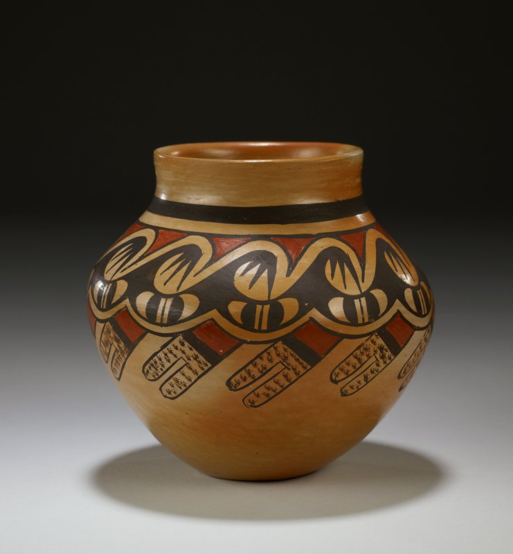 small base flaring outward and inward to short neck with wide mouth; orange body decorated with repeating geometric wavelike pattern at and below shoulder in brown and red, with textured details