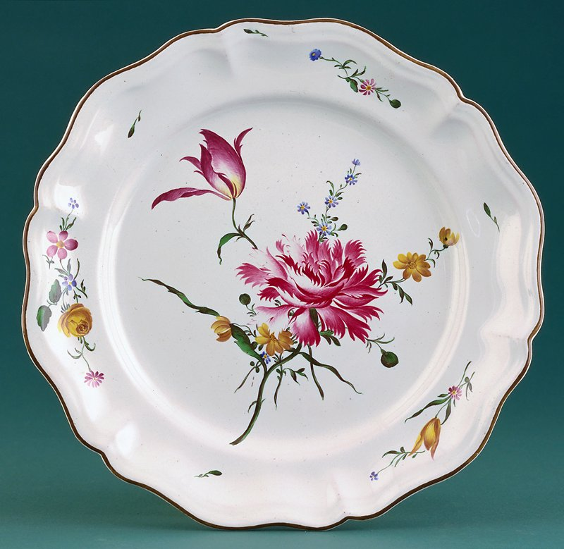 hexagonally lobed faience plate with brown glaze border and subsidiary decorative ripple effect in body of plate; center is filled with a casual arrangement of flowers a large carmine carnation, blue field daisies, buttercups and a purple parrot tulip; small sprays of fleurs fines on border