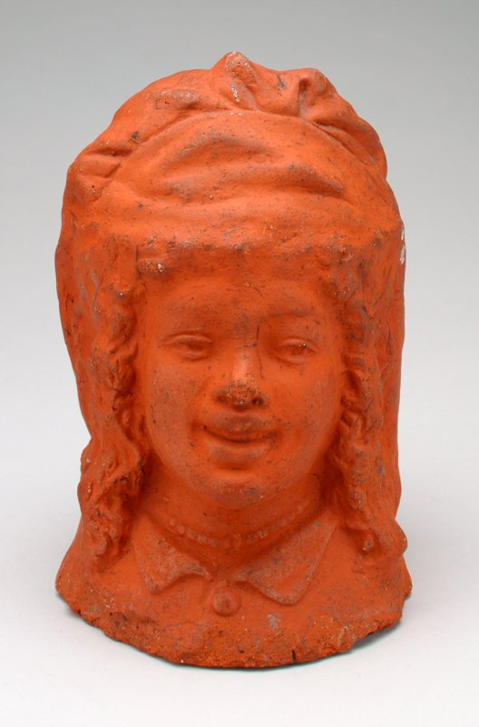 ceramic bust of a woman covered in reddish pigment; wearing a hat, a collar and beads; smiling; curly hair