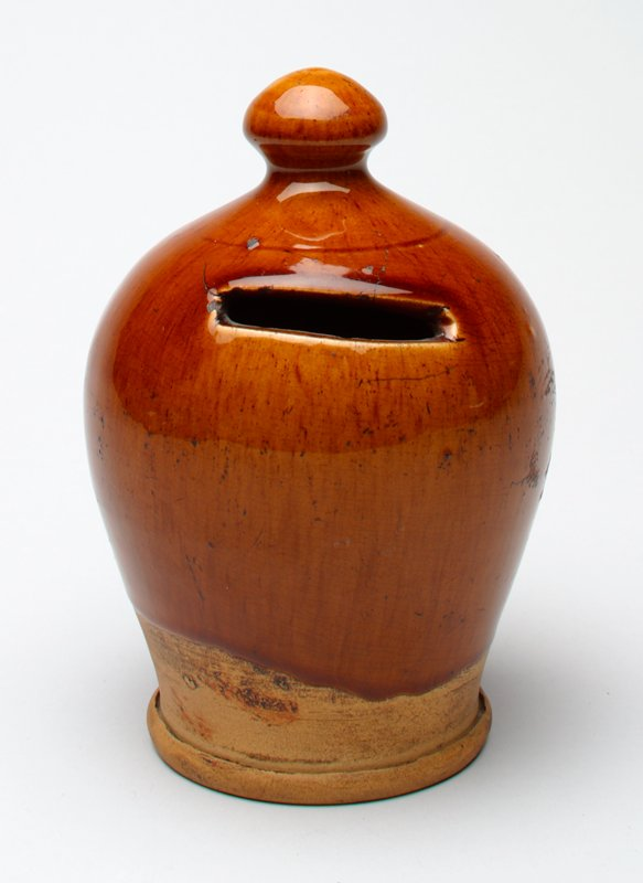 tan/brown ceramic jar with knob on top; foot is unglazed; glaze has crackle pattern;