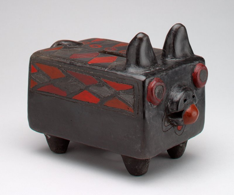 black ceramic abstract dog in rectagular shape with red eyes and tongue and red trim in the form of diamonds, triangles and circles