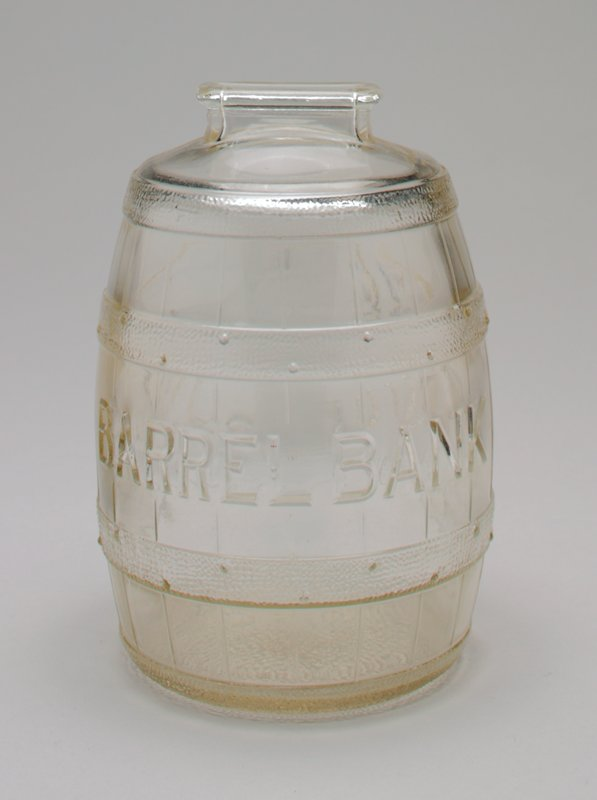 clear glass barrel with two hoops; on front and back in raised letters: 'Barrel Bank'; raised coin slot on the top