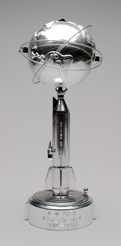 sliver rocketship with world globe above 3 ? circle globe; coin slot in base of globe; stopper in globe between Asia and Australia