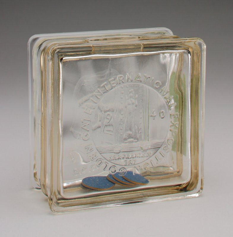 square-shaped clear glass block with: 'Golden Gate International Exposition 1940' on one side and 'Fair in '40' on the other side; paper label on one edge with instructions