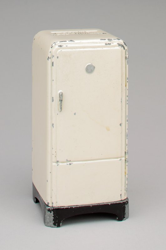 white metal refrigerator; silver handle; black base; coin slot at the top