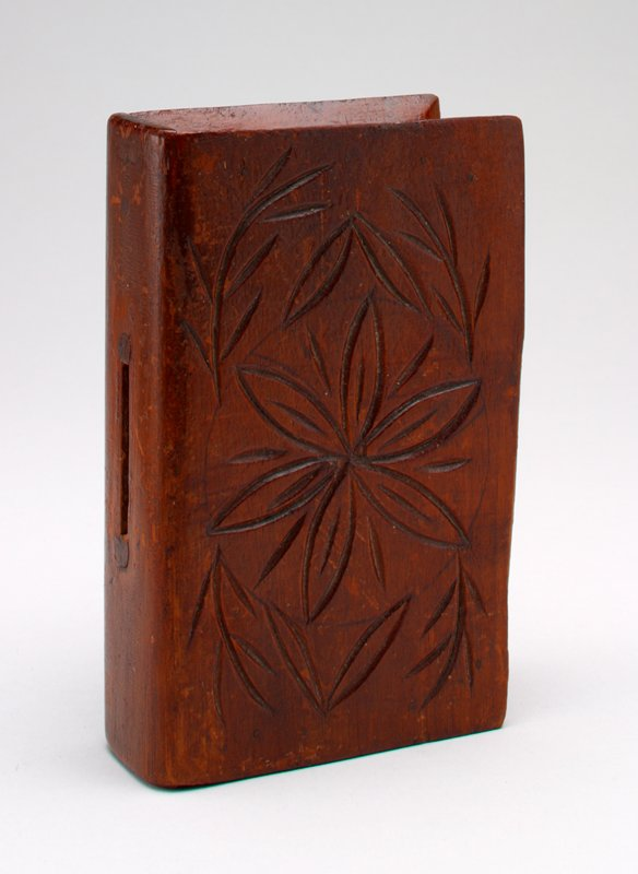 wood book shaped bank incised with flowers on front and back covers; coin slot in spine