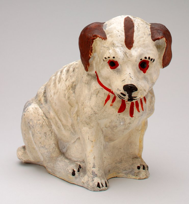 ceramic white dog with brown ears and brown streak on forehead, red around eyes, red collar; coin slot in back