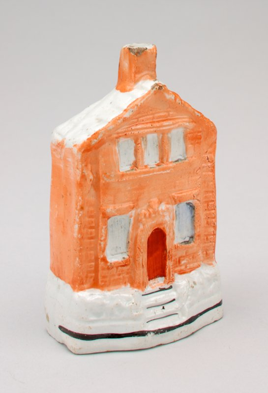 small building, peach with 2 windows and door on first story and 3 windows above; red door; coin slot behind chimney