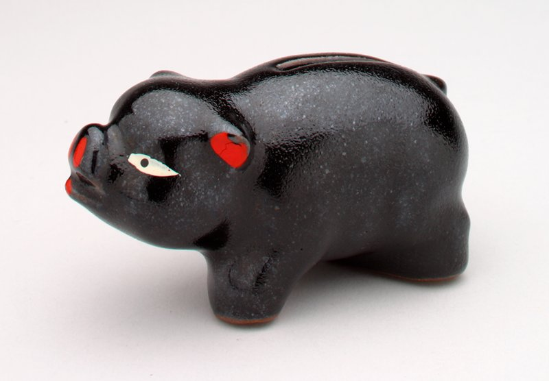black ceramic pig; white eyes; red ears, snout & tongue; coin slot in back