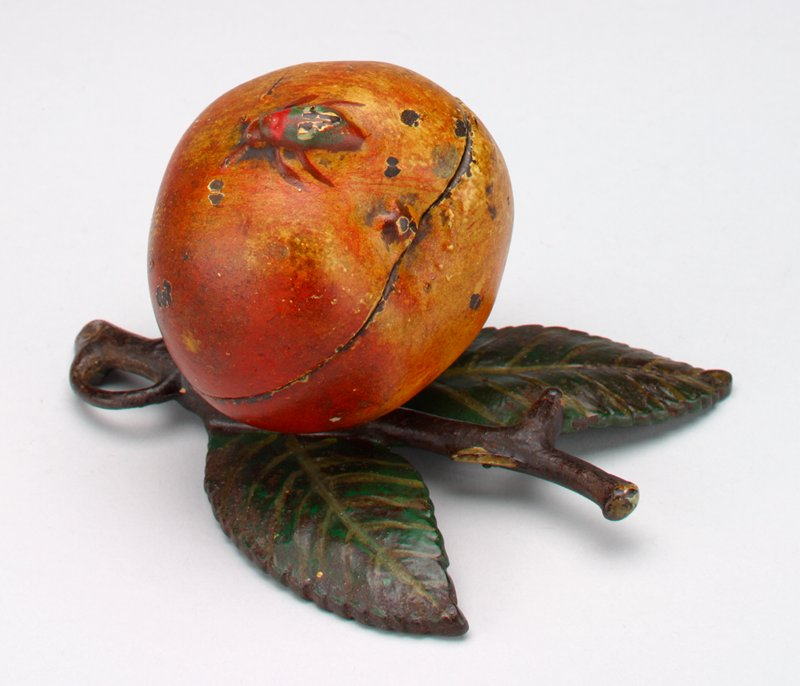 metal bank in the form of a peach with a red and green bug on it; the peach sits on a small brown branch with three green leaves