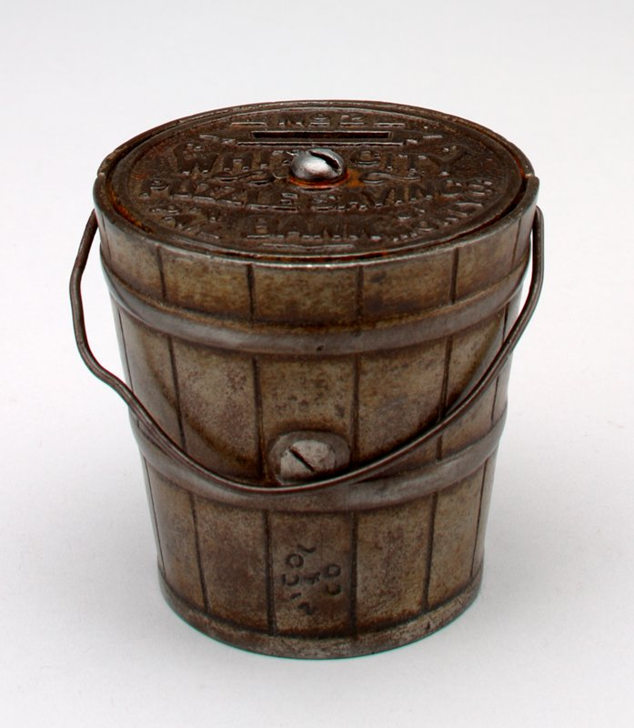 metal pail shape bank with moving handle; bronze color; coin slot in lid