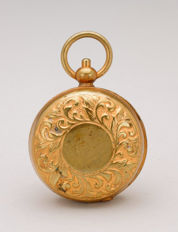 round, gold pocket watch; leaf motif around edges of cover; inside coin holder has head of a man