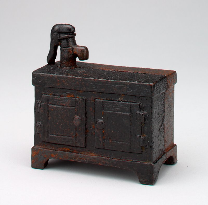 black metal chest with water pump on front and hand pump on top; doors have round knobs