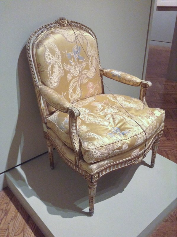 top and sides of backrest, front arm supports, apron and legs carved with architectural ornaments, flowers, scrolls and leaves, with gilding; gold satin patterned upholstery