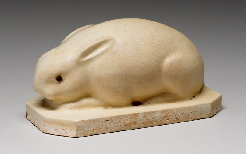 crouching rabbit with small ears and brown eyes; rectangular base with squared-off corners