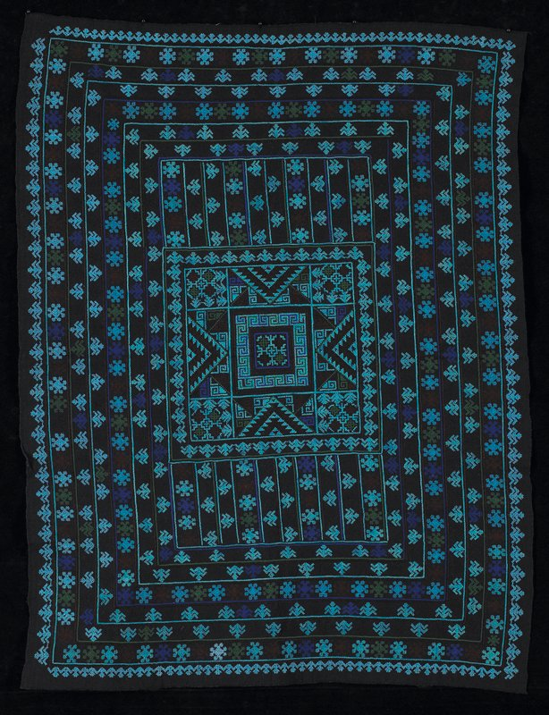 indigo fabric; cross-stitched in seven concentric bands around center square; color include blue, purple, brown and green