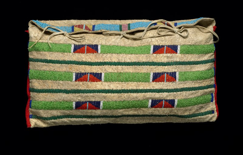 hide bag with beadwork stripes; narrow dark green stripe and wider light green with red and blue designs; red binding at sides; blue and pink beadwork stripe on flap; three hide ties to close and longer ties on back