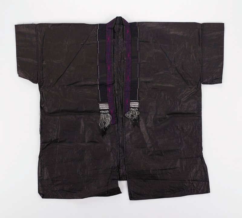 dark indigo dyed; short sleeves; geometric design with metallic strips and purple embroidery on back, with black tassels embellished with silver metal; dark pink, purple and black embroidery around collar