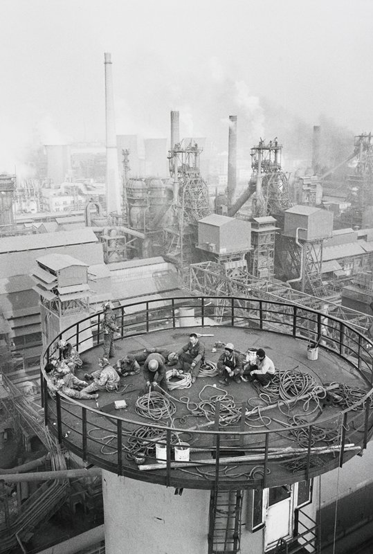 group of eleven men relaxing on circular platform in center foreground; industrial complex with smoke stacks and buildings behind; smoke and haze in background