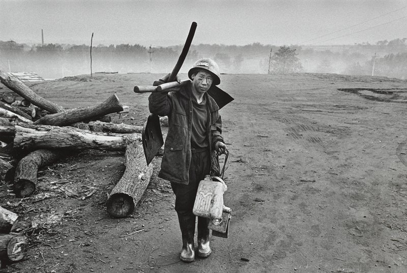 standing man wearing heavy coat, hard hat and rubber boots, carrying a shovel, plastic jugs and other tools; logs at L, barren land at R; trees in background